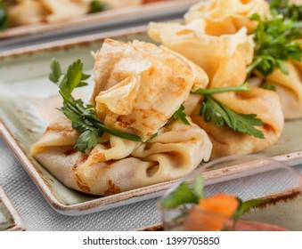 Delicious appetizers stuffed crepes with mushroom julienne sauce and greens on banquet table. Catering food, canape and snacks