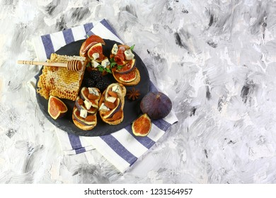 Delicious appetizers for wine or a snack - prosciutto, figs, bread, cheese on a shale board. On a gray background, top view