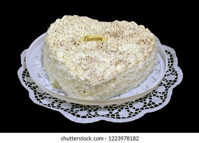 Delicious appetizing cake tiramisu, cream on a white lace napkin and a plate. Isolate on black background.