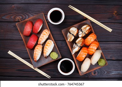 Delicious appetizing nigiri sushi set, served on clay plates with soy sauce and chopsticks, flat lay on dark wooden table. Traditional Japanese food, tasty seafood, sushi restaurant concept