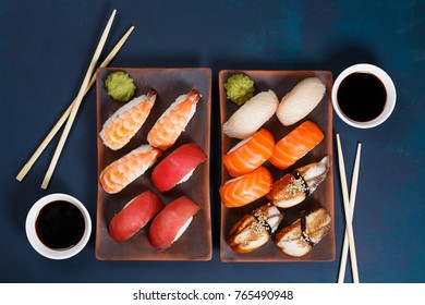 Delicious appetizing nigiri sushi set, served on clay plates with soy sauce and chopsticks, flat lay on dark green table. Traditional Japanese food, tasty seafood, sushi restaurant concept