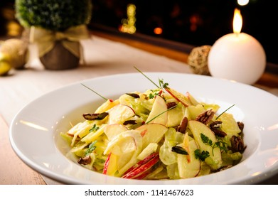Delicious apple accompaniment salad served with celery, nutty and parsley and chive on a ceramic dish. Decorated table with candles, small christmas tree and christmas balls, on a cloth background