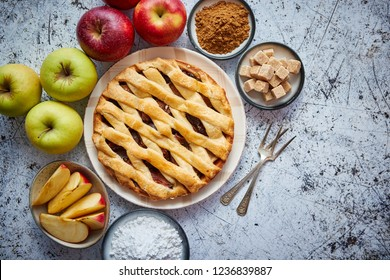 Delicious apple pie cake with a fresh red and green apples fruits, brown and powder sugar. Placed on rusty scratched stone table.