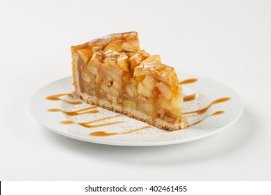 Delicious apple pie (charlotte) with caramel on the plate on white background. Close up side view.