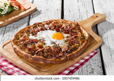 Delicious Arabic Traditional Baked Ramadan Lahmacun or Round Pide Bread with chicken egg on top serving rustic white wood background. Turkish pizza with minced beef or lamb meat, paprika and salad.