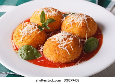 Delicious arancini rice balls in tomato sauce on a plate close-up. Horizontal