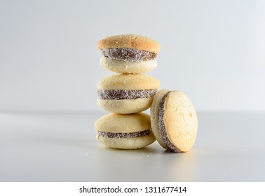 Delicious Argentinian cookies alfajores with cream dulce de leche close-up on the table. White vanilla macaroons on wooden background. French delicate dessert for Breakfast in the morning light.