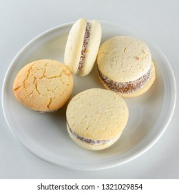 Delicious Argentinian cookies alfajores with cream dulce de leche close-up on the table. White vanilla macaroons on white background. French delicate dessert for Breakfast in the morning light.