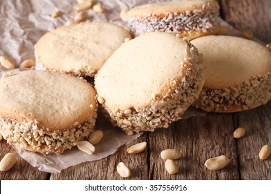 Delicious Argentinian cookies alfajores with cream on paper close-up on the table. Horizontal