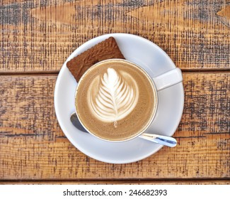 delicious art capuccino coffee cup on wooden background, space for typing