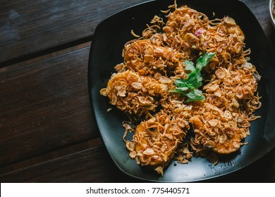 Delicious Asian - Asia eating Thai food. Crispy shrimp with sweet tamarind sugar sauce. Served with chili fried, crispy onion and green vegetable fried on a plate and wooden table background.