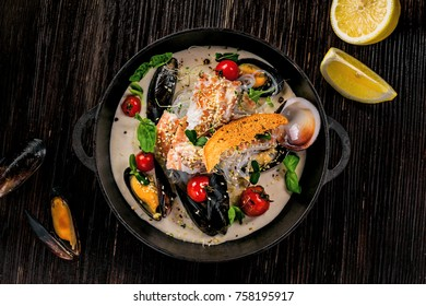 Delicious Asian meal made of sea bass fish, mussels, crab meat and other seafood with tomato and rice noodles on a rustic wooden table. Top view.
