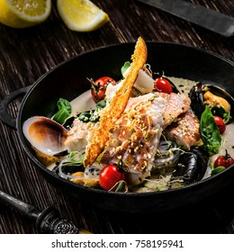 Delicious Asian meal made of sea bass fish, mussels, crab meat and other seafood with tomato and rice noodles on a rustic wooden table.
