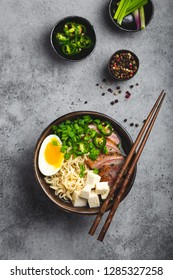 Delicious Asian noodle soup ramen in bowl with meat broth, tofu, sliced pork, egg with yolk, grey rustic concrete background, close up, top view. Hot tasty Japanese ramen soup for dinner asian style