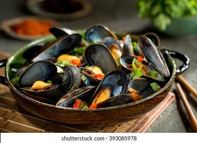 Delicious asian style steamed mussels with red pepper, green onion, and coriander in a coconut broth.