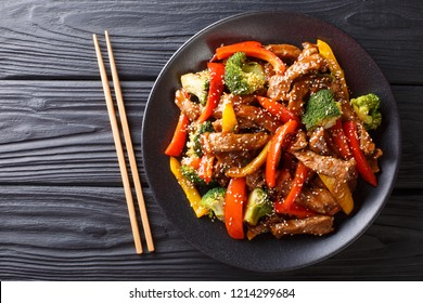 delicious Asian teriyaki beef with red and yellow bell peppers, broccoli and sesame seeds close-up on a plate on the table. Horizontal top view from above