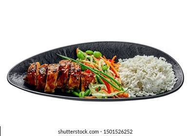 Delicious Asian teriyaki chicken, salad made of cucumber, carrot, ginger, pepper and cabbage, edamame, sesame and rice in a black pottery plate isolated on white background.