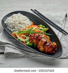 Delicious Asian teriyaki chicken, salad made of cucumber, carrot, ginger, pepper and cabbage, edamame, sesame and rice in a black pottery plate.