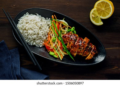 Delicious Asian teriyaki chicken, salad made of cucumber, carrot, ginger, pepper and cabbage, edamame, sesame and rice in a black pottery plate. Top view, directly above.