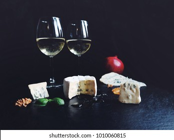 Delicious assorted cheese with fresh fruits on a black stone background. White wine glasses, Gorgonzola, blue Roquefort, Brie cheese with honey. Appetizers, sliced cheese on a plate.