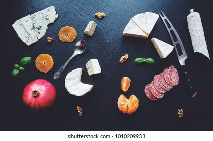 Delicious assorted food on a black stone board. Cheese, salami, fruits. Various appetizers. Snacks/short cuts. Top view.