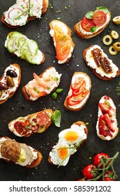 Delicious assortment of different canapes topped with egg, tomato, prawns, salmon, chorizo, radish, cucumber and olives on quark or cream cheese and crusty bread viewed on slate from above