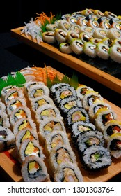 Delicious assortment of sushi rolls lined up on a buffet table ready for eating.
