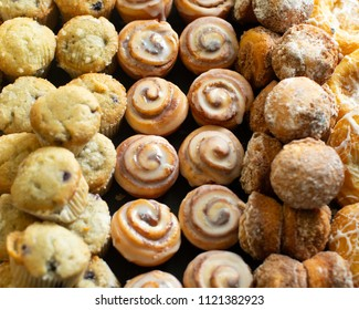 A delicious assortment of sweet and sugary breakfast pastries, cinnamon rolls, and muffins.