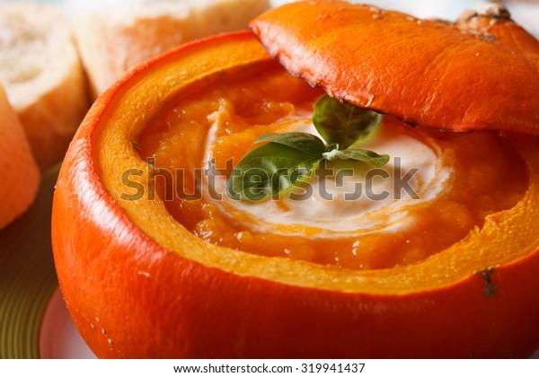 Delicious autumn baked pumpkin soup macro on a plate. horizontal