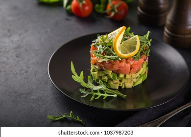 delicious avocado and salted salmon tartar, served with arugula, dark background, selective focus