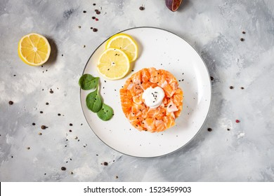 Delicious avocado and salted salmon tartar on concrete background