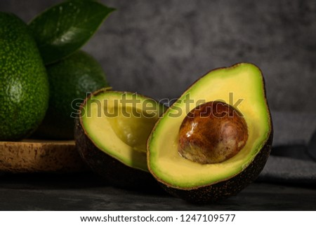 Delicious avocados in a cork plate on kitchen countertop.