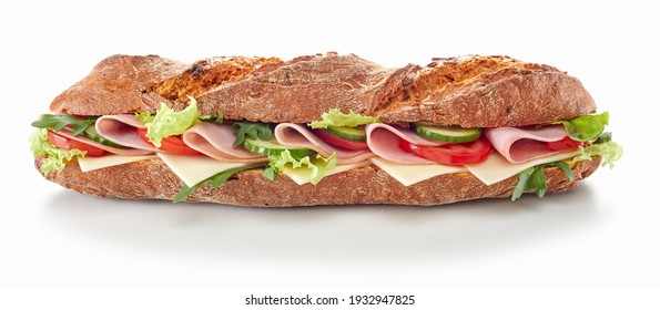 Delicious baguette sandwich with various ripe vegetables and ham slices served on white table in studio