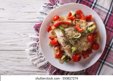 Delicious baked flounder with seasonal vegetables on a plate. horizontal view from above