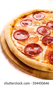 Delicious baked pizza on a white board and a menu of various fresh gourmet ingredients.