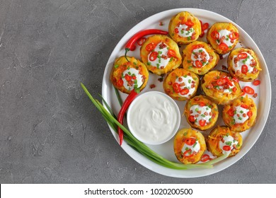 delicious baked potato halves loaded with grated cheddar cheese, bacon, chili peppers slices, sour cream on white plate, on concrete background, view from above, close-up