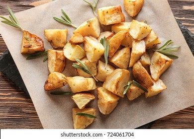 Delicious baked potatoes with rosemary on slate plate, closeup