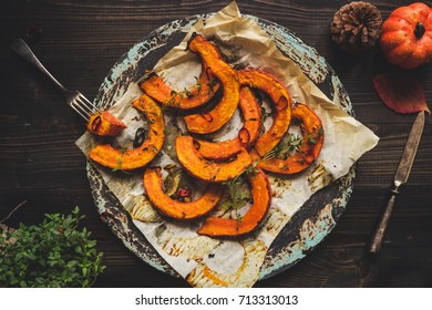 Delicious baked pumpkin with thyme and chili on the wooden table, top view.