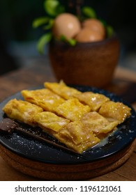Delicious banana pancake with eggs and honey on black plate wooden with serving spoon