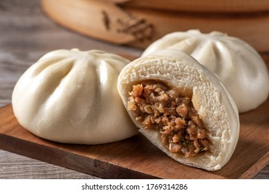 Delicious baozi, Chinese steamed meat bun is ready to eat on serving plate and steamer, close up, copy space product design concept.