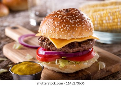 A delicious barbecue cheeseburger with lettuce, tomato and onions.