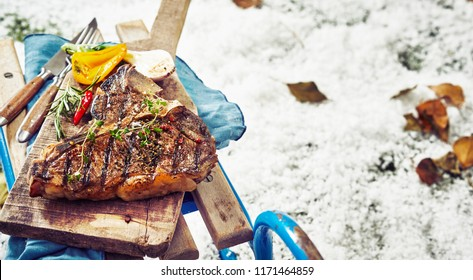 Delicious barbecued marinated t-bone steak seasoned with herbs and served with grilled vegetables on a wooden board on a sled at a winter barbecue outdoors in the snow with copy space