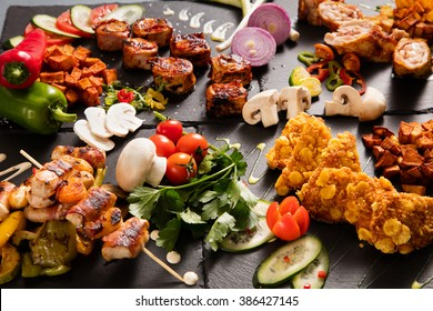 Delicious barbecued meat served on black stone plates decorated with vegetables and mushrooms