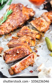 Delicious barbecued ribs seasoned with a spicy basting sauce and served with chopped fresh vegetables lined on an parchment in a baking sheet in a country kitchen