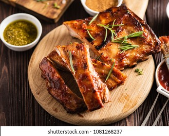 Delicious barbecued ribs seasoned with a spicy basting sauce and served with chopped fresh vegetables on an old rustic wooden chopping board.