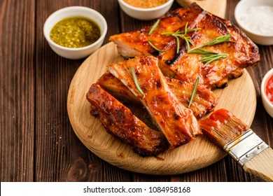 Delicious barbecued ribs seasoned with a spicy basting sauce and served with chopped fresh vegetables on an old rustic wooden chopping board