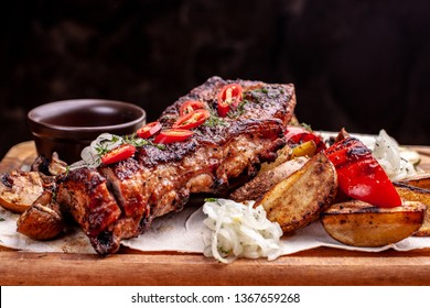 Delicious barbecued ribs seasoned with a spicy basting sauce and served with chopped fresh herbs on an old rustic wooden chopping board in a country kitchen.