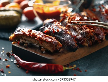 Delicious barbecued ribs seasoned with a spicy basting sauce and served with chopped fresh vegetables on an old rustic wooden chopping board in a country kitchen.  Vintage toned