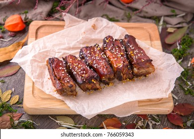 Delicious barbecued ribs seasoned with a spicy basting sauce. Beautiful stylish menu. Autumn still life. Free space for text
