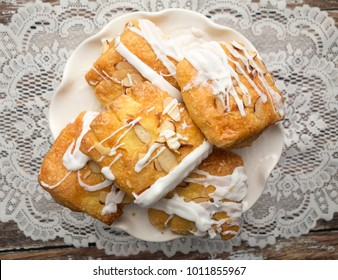 Delicious bear claw pastries with white icing and almonds on a white dish with lace background.